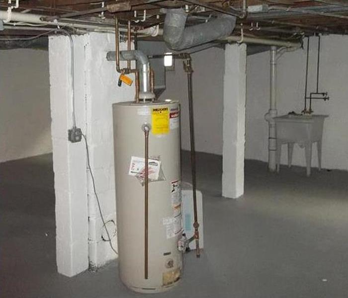 clean basement, no evidence of flooding, water heater and sink in view