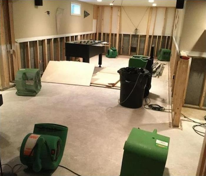 SERVPRO drying equipment in a basement with the framework exposed