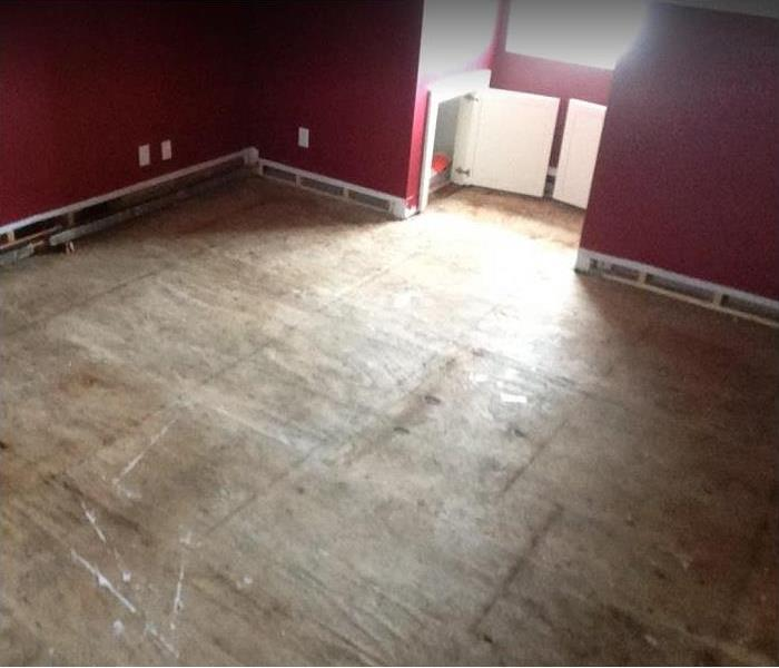 water damaged room; flooring stripped to subfloor; baseboards removed